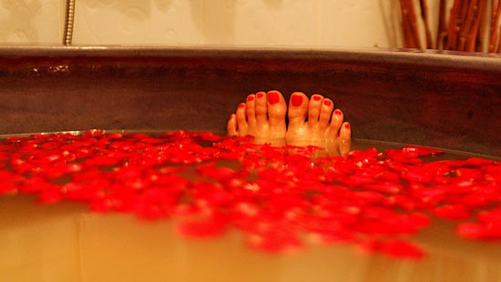 Toes sticking out of a rose petal covered bathwater